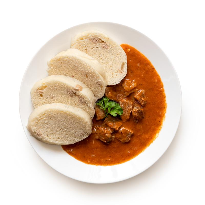 Beef goulash with bread dumplings and parsley garnish on white ceramic plate isolated on white. Top view.  stock photo