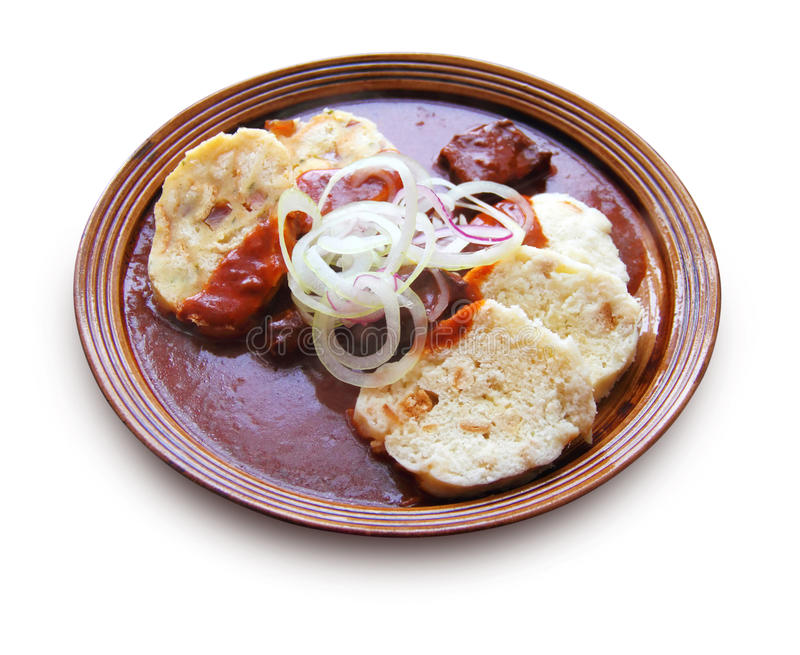 Beef goulash with gravy and bread and potato dumplings. Isolated on white background with clipping path stock image