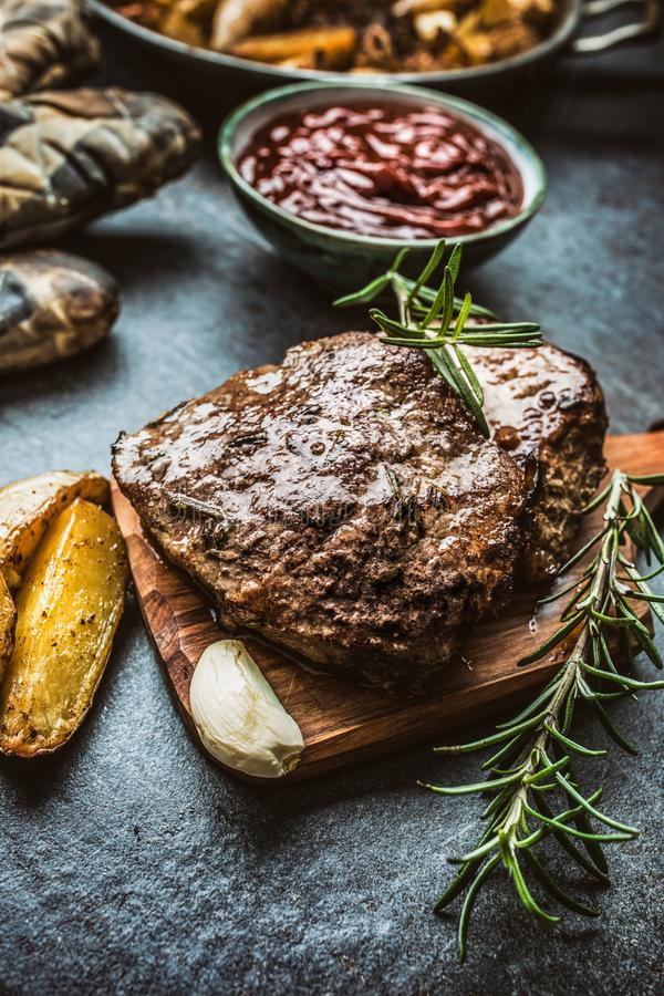 Beef grilled steaks with barbecue sauce roasted potatoes and rosemary.  stock images