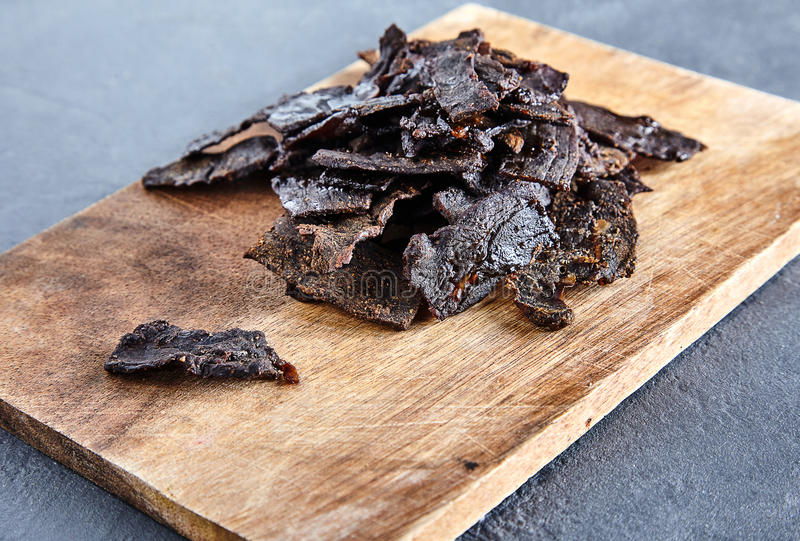 Beef jerky on wood board and royalty free stock photo