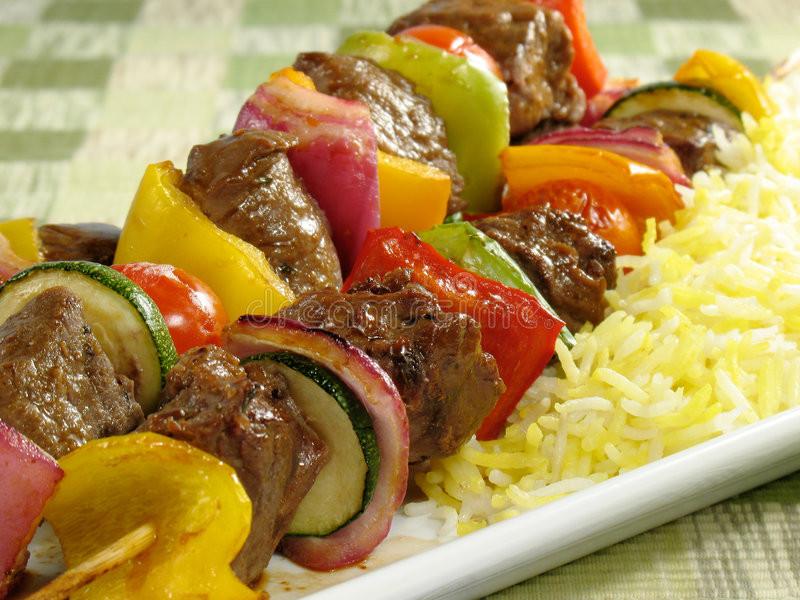 Beef Kebab and Saffron Rice. Juicy beef kebabs with bell peppers, onions, zucchini, and cherry tomatoes. Accompanied by a bed of saffron flavored basmati rice stock image