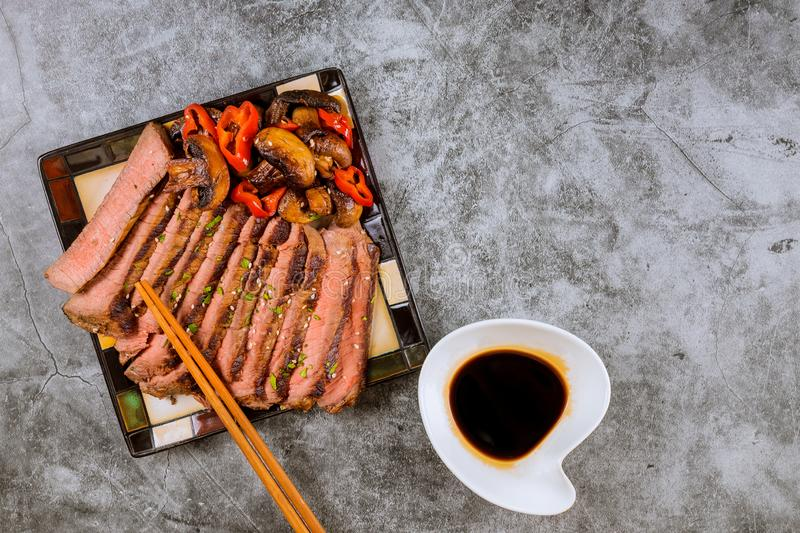 Beef Korean grilled beef made thinly sirloin of steak fried in red bell peppers and mushrooms on plate with chopsticks stock photography