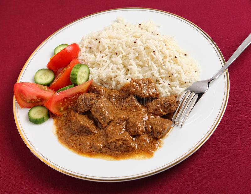 Beef korma, basmati and salad meal. A meal of north Indian or Pakistani-style beef korma curry with basmati rice and a tomato and cucumber salad royalty free stock images