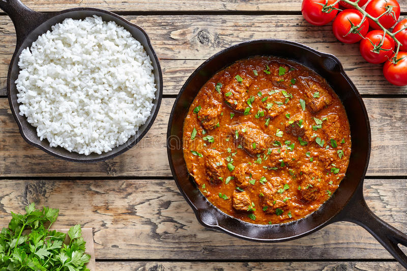 Beef Madras curry slow cook Indian spicy garam masala lamb food in cast iron pan. On vintage wooden table background. Traditional India culture restaurant dish stock photos
