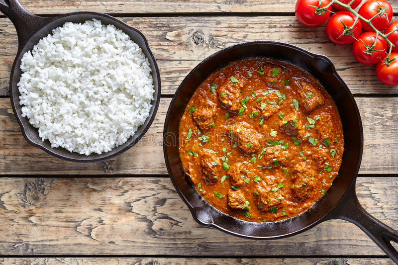 Beef Madras traditional slow cook Indian spicy chili lamb meat food with rice and tomatoes stock images