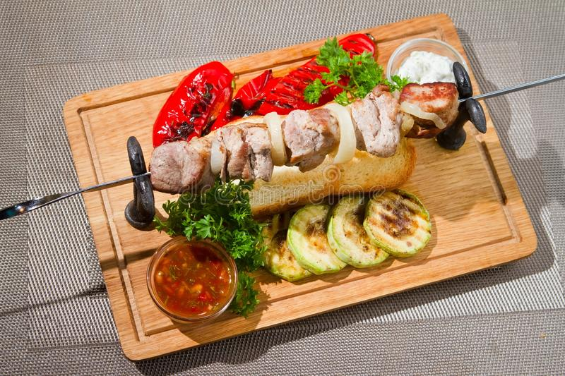 Beef meat barbecue with grilled zucchini, paprika, toast bread, parsley and sauce, served on wooden plate in restaurant stock photo