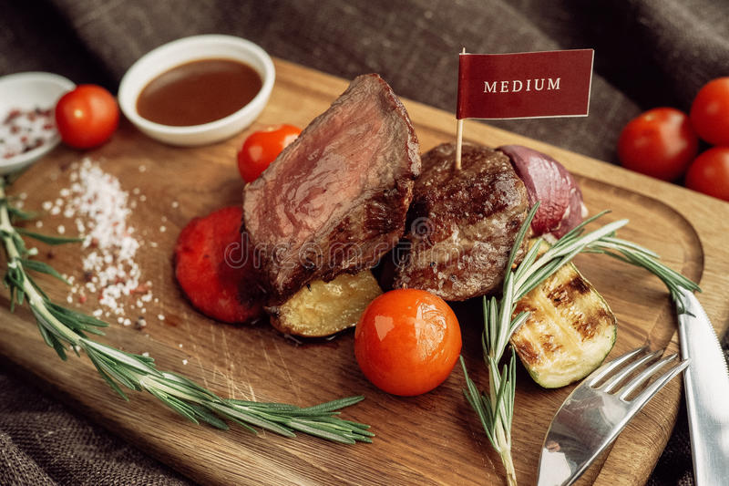 Beef meat fillet mignon cutted on wooden plate. With fork many different kinds of dry spice over table stock images