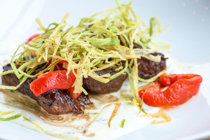 Beef medallions with greens. Fry, red boiled pepper and white cheese sauce on a white plate, brown bread, restaurant table, close up royalty free stock images