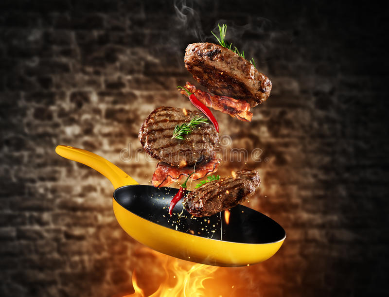 Beef milled meat flying from a pan. With flames, grunge old brick wall on background royalty free stock photography