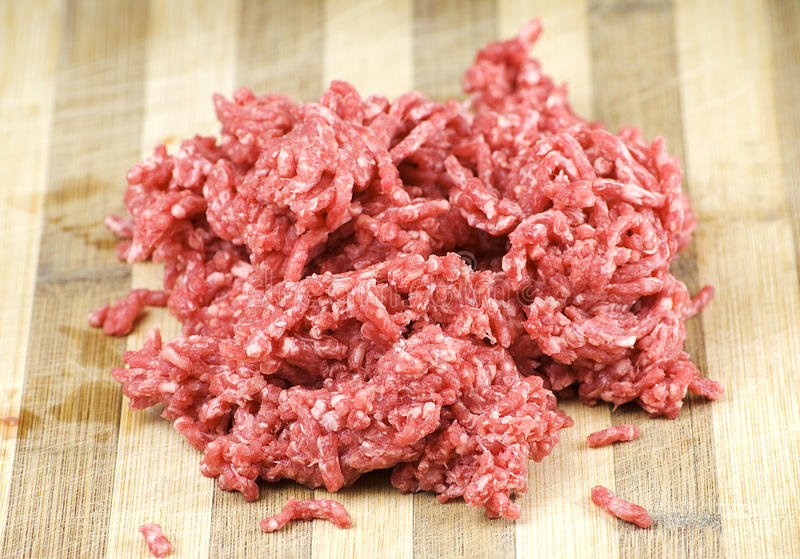 Beef mince. Pile of fresh raw beef mince over wooden kitchen board stock photos