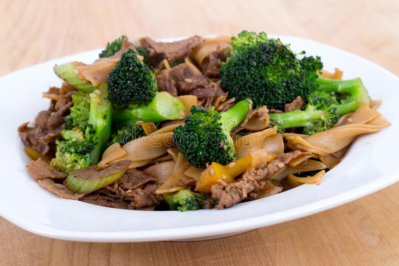 Beef Pad Sew stir fry. Bowl with broccoli and vegetables royalty free stock image