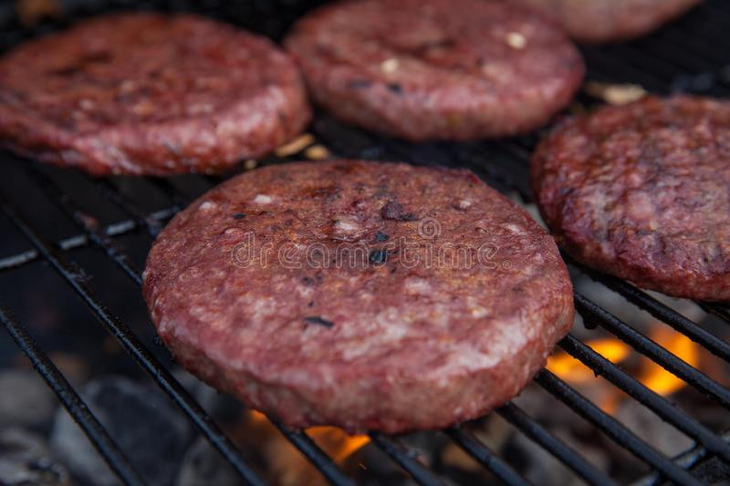 Beef or pork meat barbecue burgers for hamburger prepared grilled on flame grill. Beef or pork meat barbecue burgers for hamburger prepared grilled on bbq fire stock photos