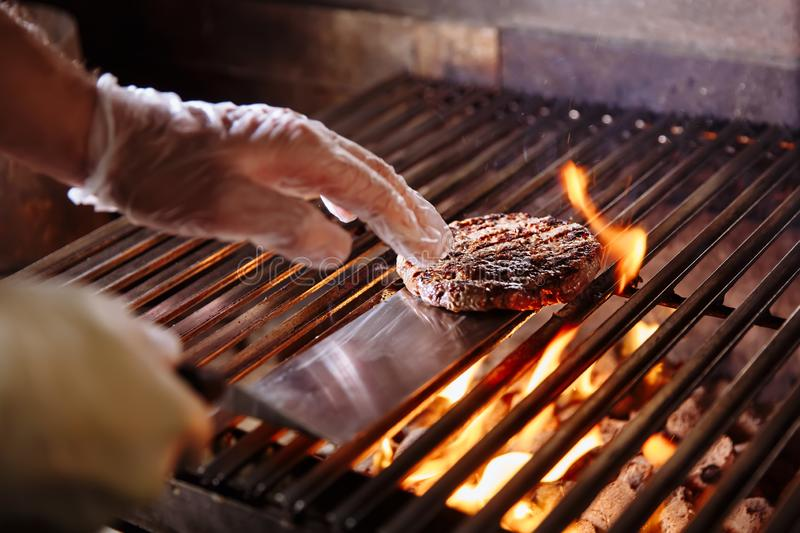 Chef making burger. Beef or pork meat barbecue burgers for hamburger prepared grilled on bbq fire flame grill. Close-up royalty free stock photography