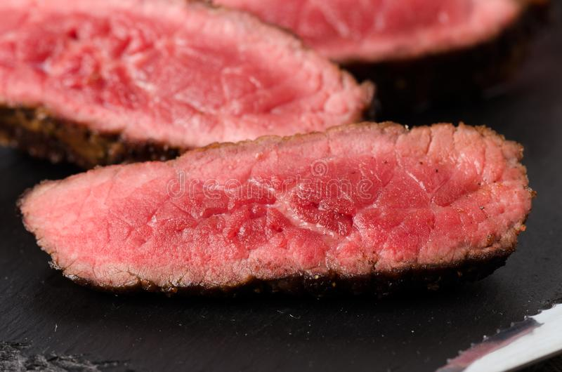 Beef rare steak sliced close up. Black angus rare steak sliced dark plate on a black background stock photography