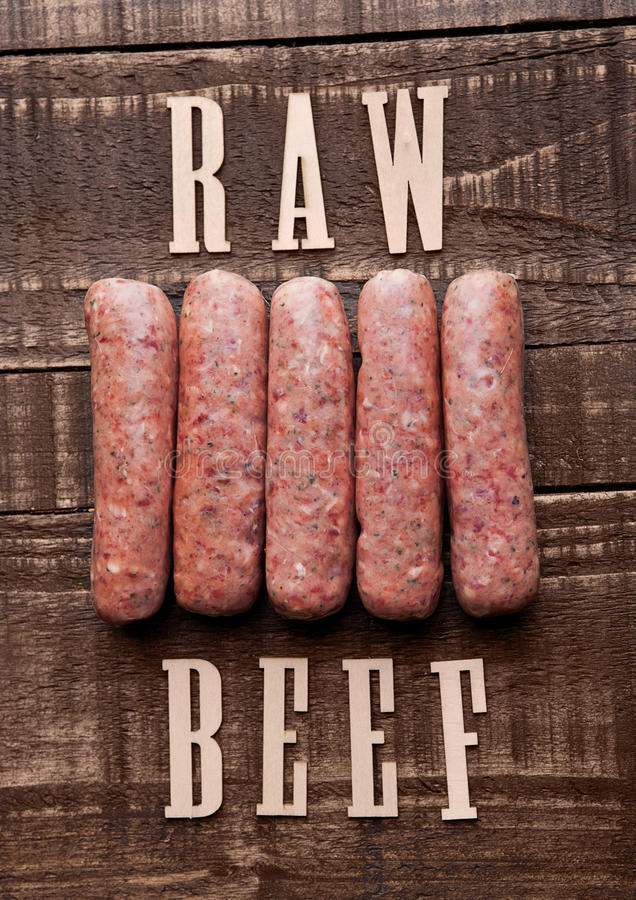 Beef raw sausages on grunge wooden board with letters stock images