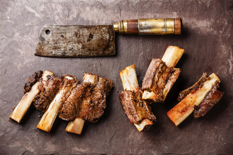 Beef Ribs BBQ and Meat cleaver. Beef Ribs BBQ and Butcher Meat cleaver on stone slate background stock photos