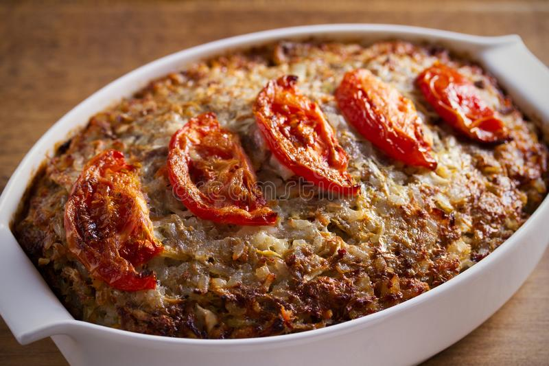 Beef rice and cabbage casserole in white baking dish on wooden table. royalty free stock photography