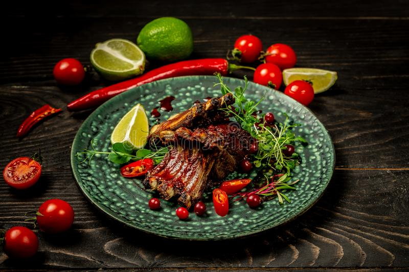 Beef Short Ribs with a in sour sweet berry sauce served with green seedlings on the plate. Shallow Depth of Field. concept of royalty free stock images