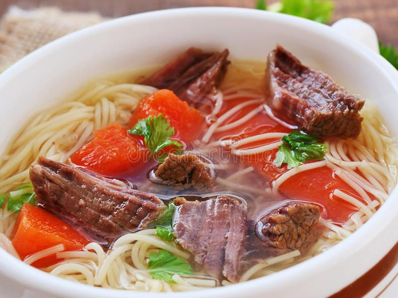 Beef soup with noodles and vegetables in soup bowl. Closeup stock photography