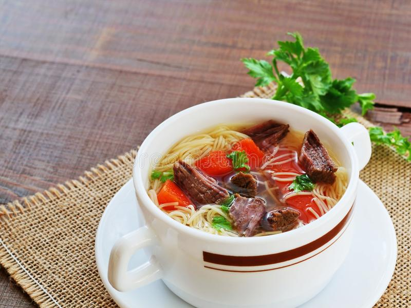Beef soup with noodles and vegetables in soup bowl. Over wooden table royalty free stock photo