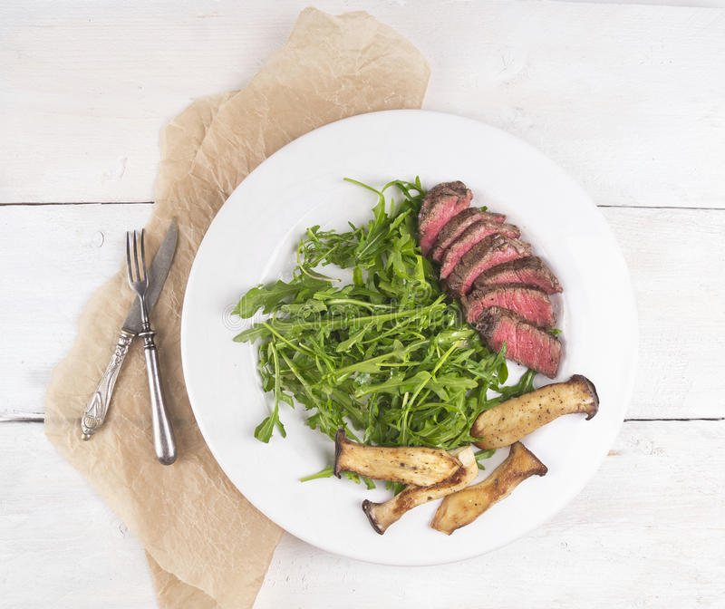 Beef steak with arugula and mushrooms stock photography