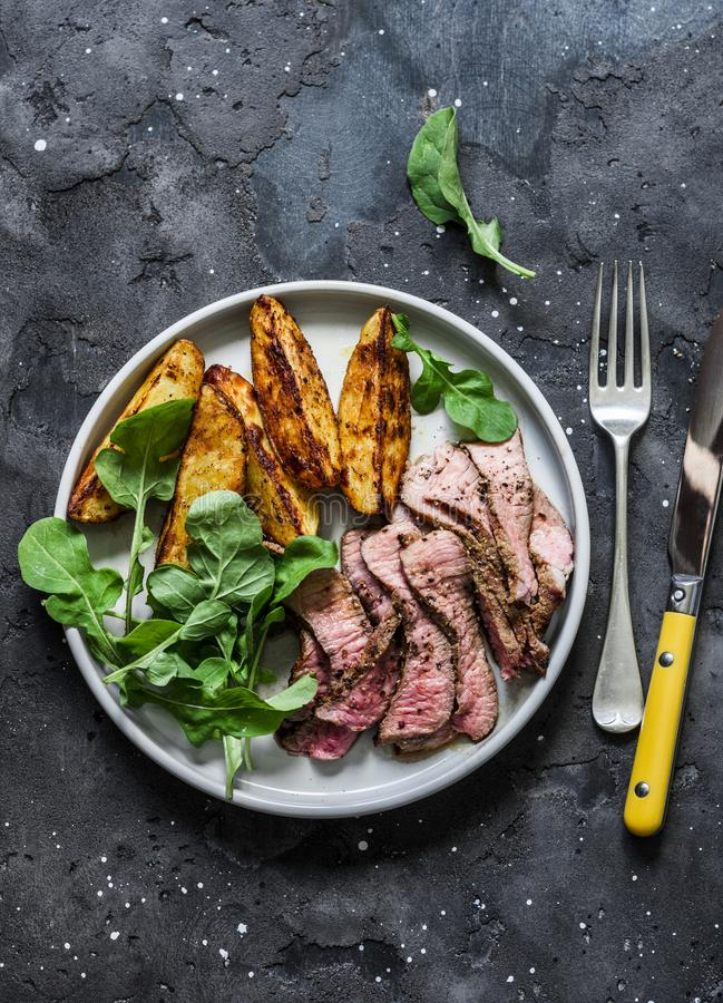 Beef steak and baked young potatoes - delicious lunch on a dark background, top view royalty free stock images