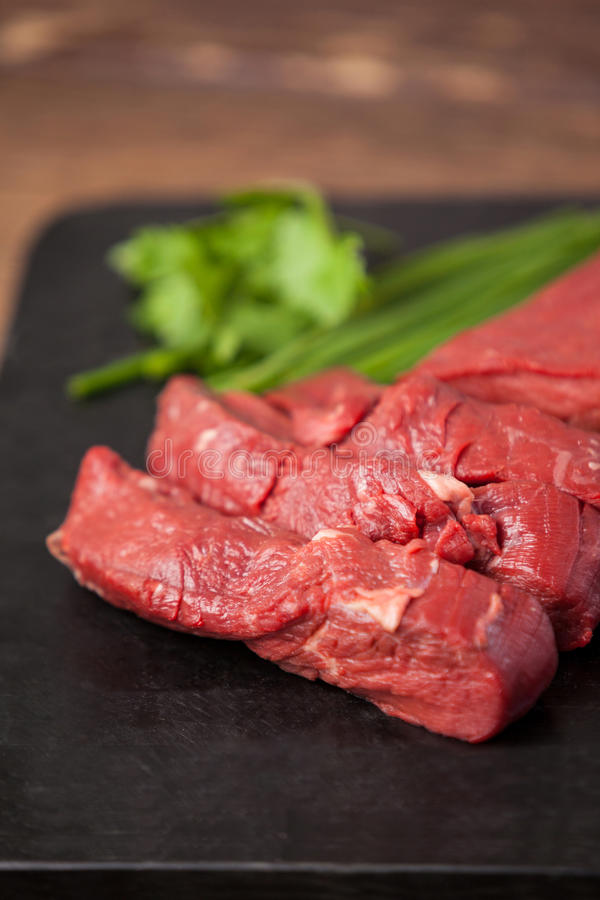 Beef steak on black slate plate. Against wooden background royalty free stock image