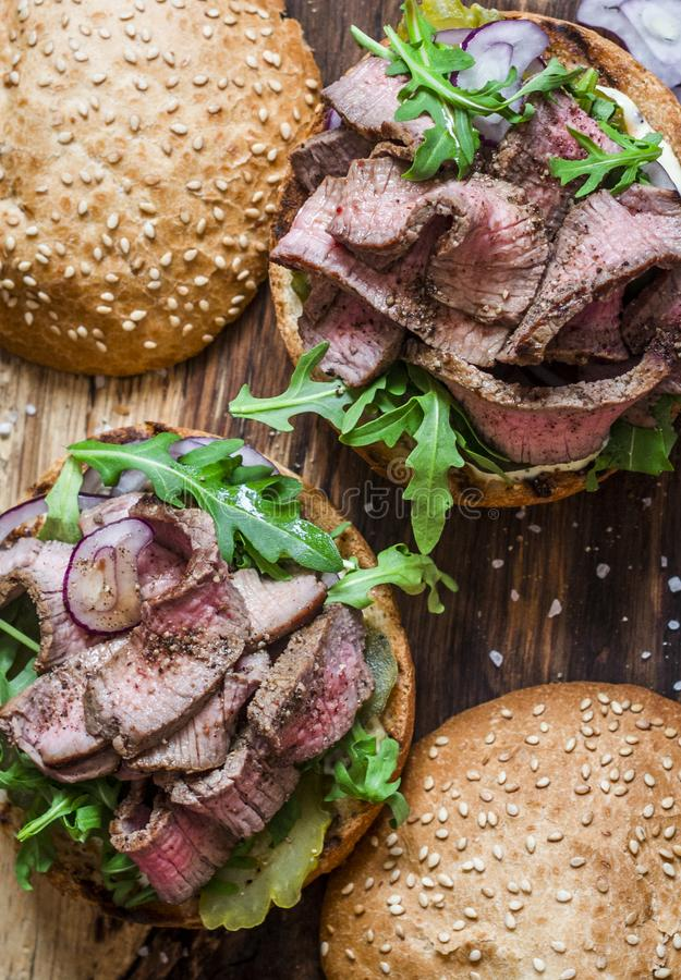 Beef steak burger with pickles, mayo sauce, arugula and red onion on a rustic wooden board, top view. royalty free stock images