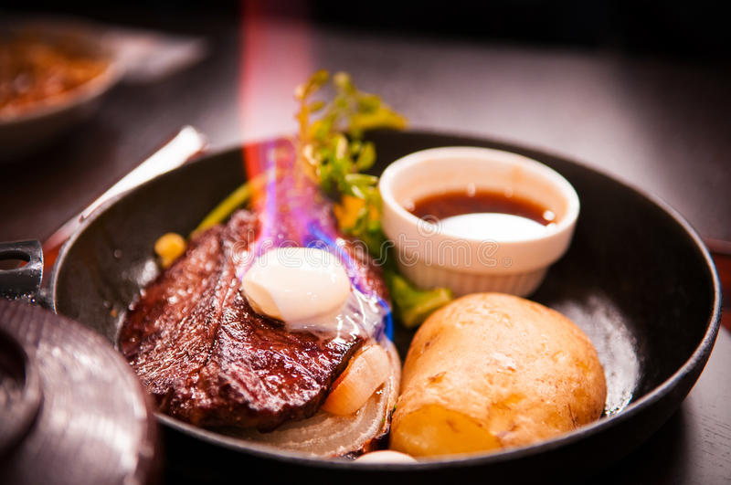 Beef steak with burning butter on top royalty free stock photo