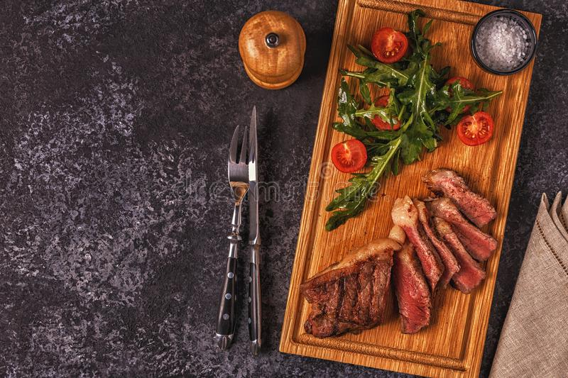 Beef steak on a dark background. Top view, copy space stock photography