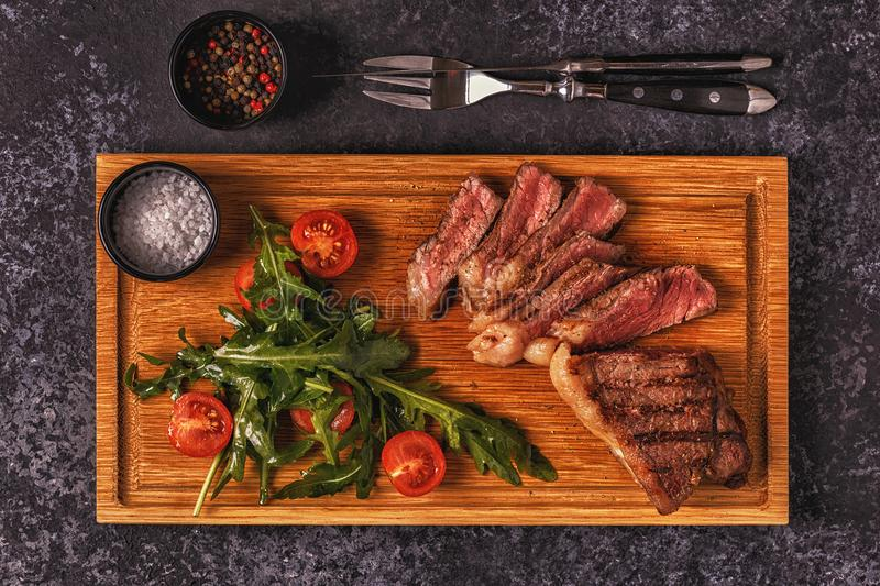 Beef steak on a dark background. Top view, copy space royalty free stock images