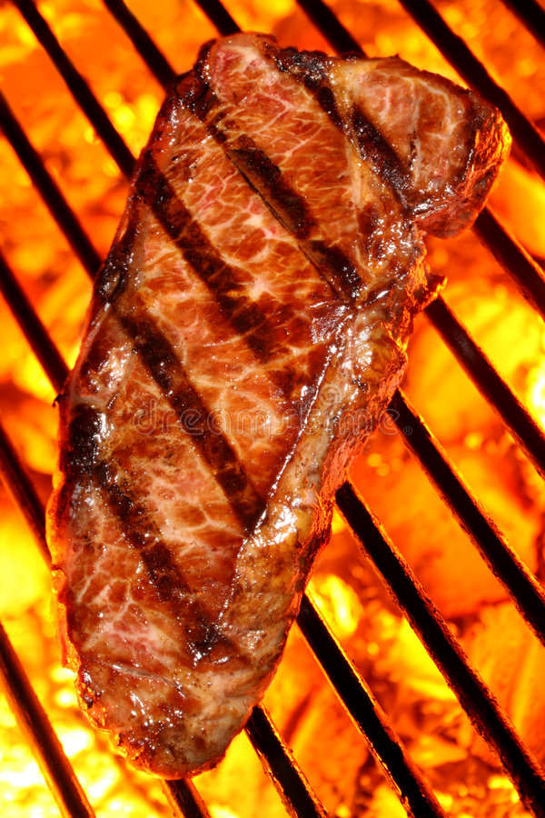 Beef steak on a fire hot barbecue grill. Close shot of a grilled beef steak with grill marks on a barbecue grill over fire hot charcoal. Barbecue & Outdoor stock images