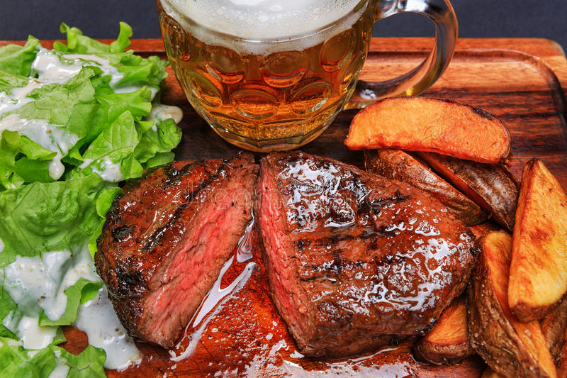 Beef steak with french fries and beer stock images