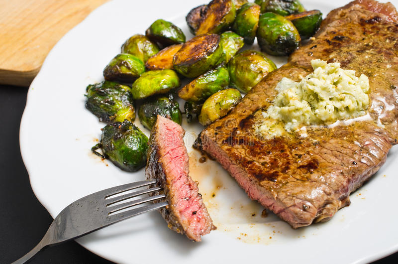 Beef steak with garlic butter and brussel sprouts. Delicious beef steak with garlic butter and brussel sprouts royalty free stock images