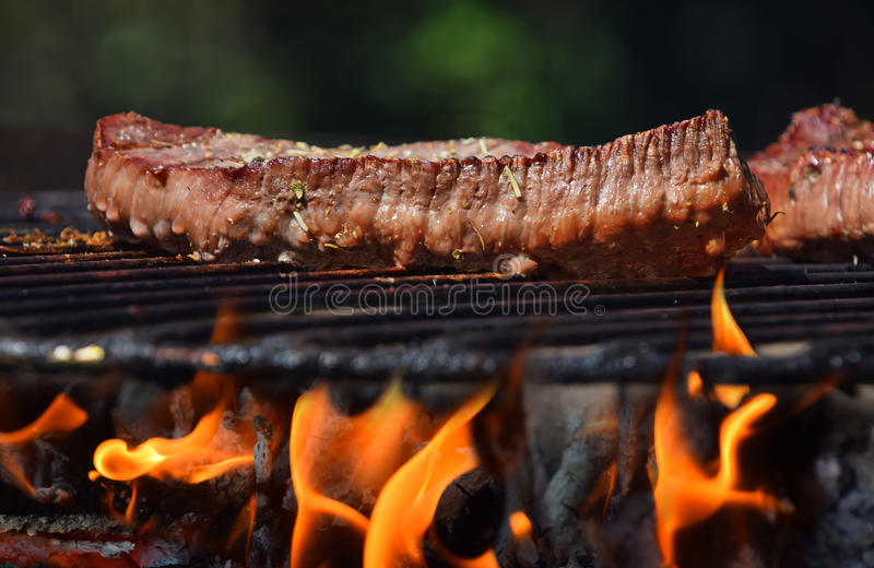 Beef steak grilled on flame barbecue fire grill stock photography