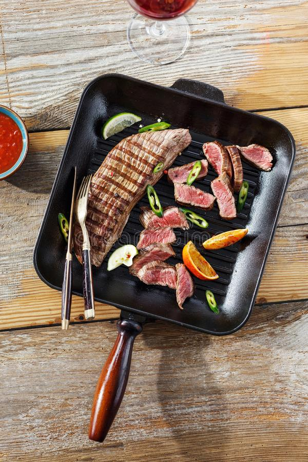 Beef steak grilled grill pan wooden table glass red wine sauce t royalty free stock images