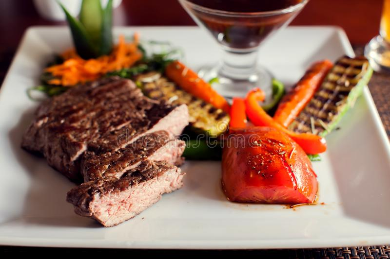 Beef steak with grilled vegetables served on white plate. Food concept royalty free stock image