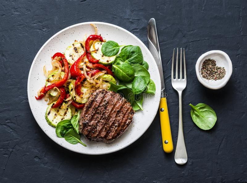 Beef steak with grilled vegetables, sweet pepper, zucchini and fresh spinach on a dark background. Delicious healthy royalty free stock photography