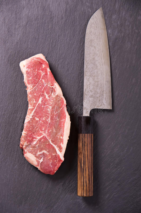 Beef Steak with Japanese Santoku Knife. As closeup on black background royalty free stock photography