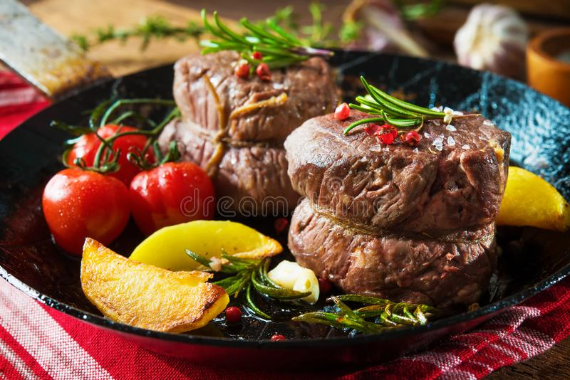 Juicy medium beef fillet steaks mignon in pan on table royalty free stock photos