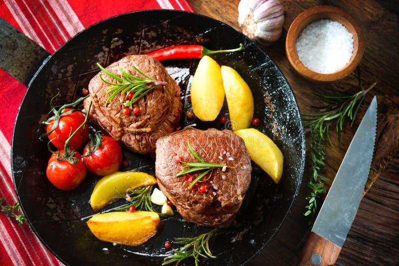 Juicy medium beef fillet steaks mignon in pan on table. Beef steak. Juicy medium beef fillet steaks mignon in pan on table stock images