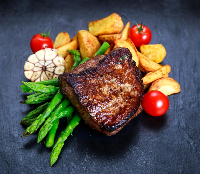 Beef steak Mignon cooked with Asparagus, potatoes, garlic and tomatoes. royalty free stock photos