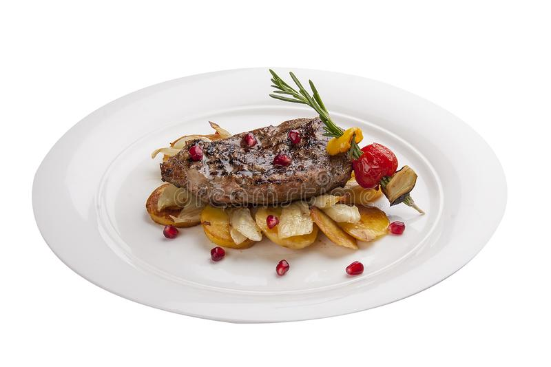 Beef steak with potatoes on a white plate royalty free stock photography