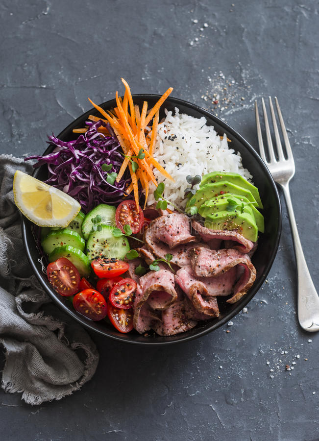 Beef steak, rice and vegetable power bowl. Healthy balanced food concept. On a dark background royalty free stock image