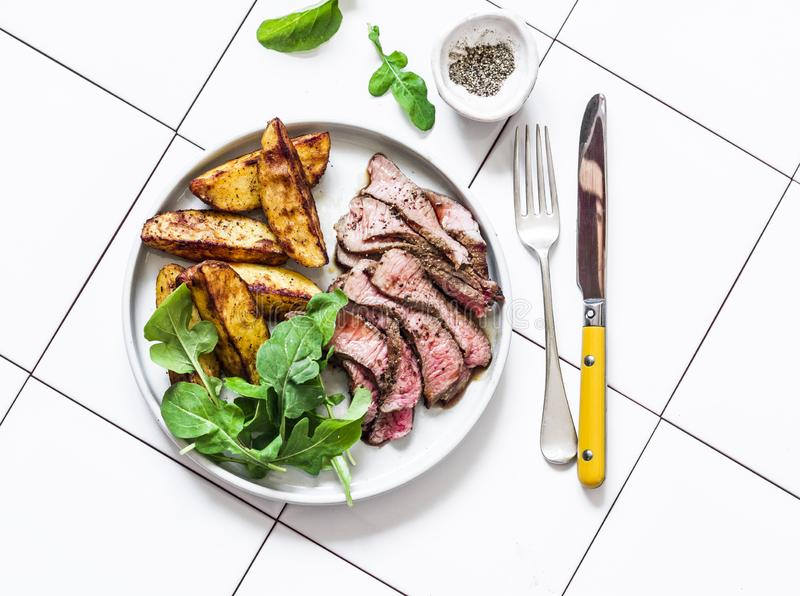 Beef steak and roast new potatoes - delicious lunch on a light background, top view royalty free stock images
