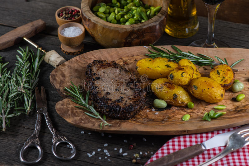 Beef steak with roasted potatoes. In rustic kitchen stock image