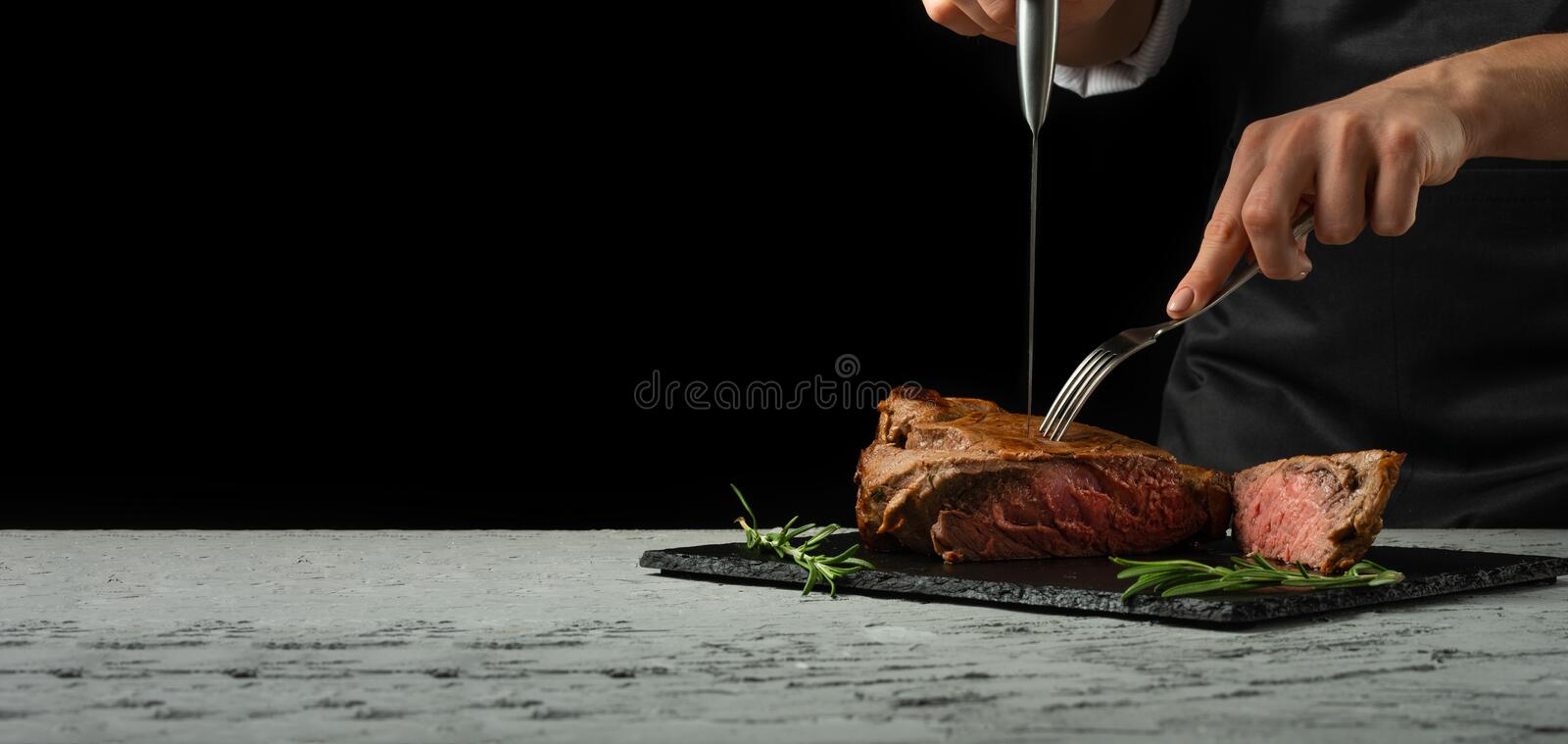 Beef steak with rosemary on a black background with open space for text or restaurant menus. Horizontal photo Black text area.Bane. R royalty free stock image
