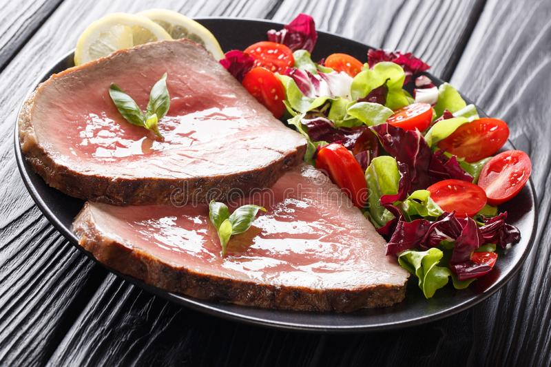 Beef steak is served with a summer vegetable salad close-up on a. Plate on a black table. horizontal stock photos