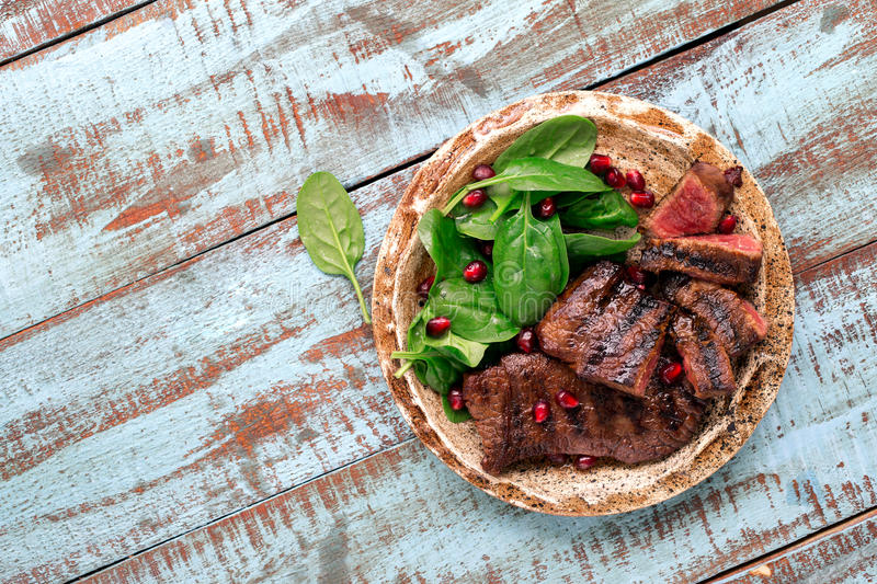Beef steak with spinach leaves and pomegranate in plate royalty free stock photo
