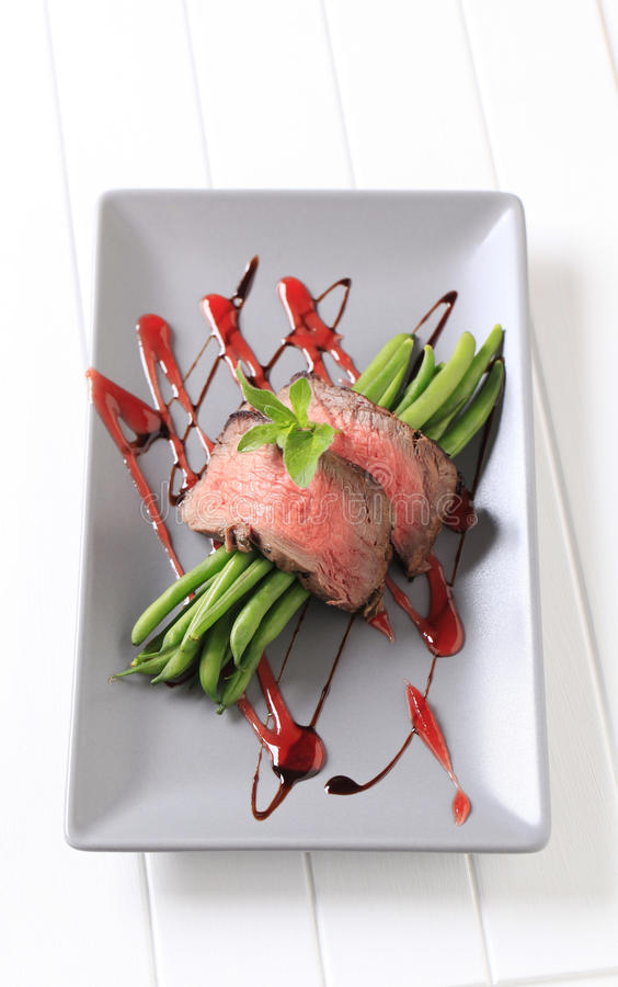 Beef steak and string beans. Slices of medium rare beef steak and string beans stock image